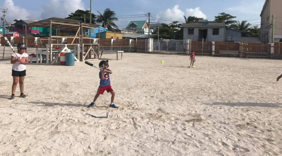 A child in Belize plays baseball taught by Projects Abroad volunteers